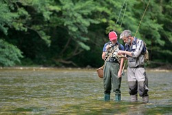 A father and his son fly fishing in summer on a beautiful trout river with clear water