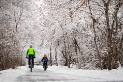 A father and his son ride a bikes in a winter park. Back view. Weekend in a snowy park