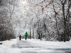 A father and his son ride a bikes in a winter park. Weekend in a snowy park