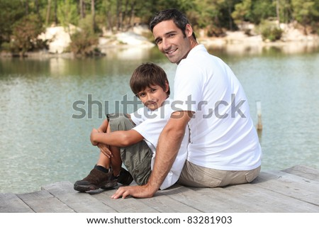 a father and his son seated on a pontoon faces a lake - stock photo