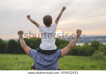 A Father and son having fun outdoors in the meadow #659652421