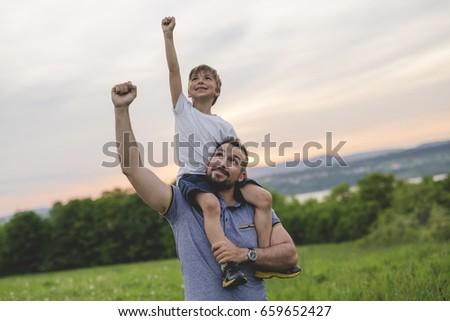 A Father and son having fun outdoors in the meadow