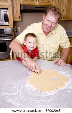 A father and son making cut out cookies.