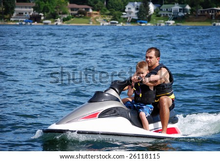a father and son take a ride on a personal water craft