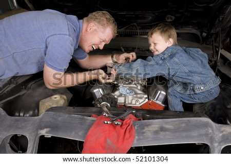 A father and son working together restoring an engine, with happy expressions on their faces.