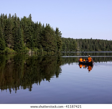 A father and two kids paddle in Pog Lake, in Algonquin Park, Ontario Canada.