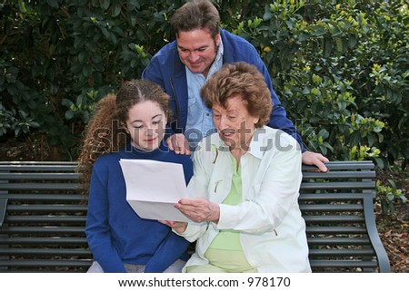 A father, daughter and grandmother reading together in the park.  Horizontal orientation.