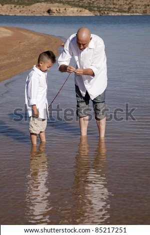 A father fixing his sons pole so he can fish.