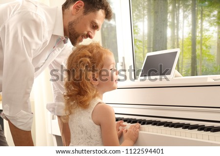 A Father giving Daughter Piano lessons