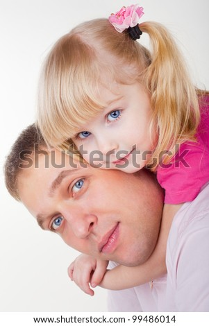 A father holding daughter on shoulders on white background