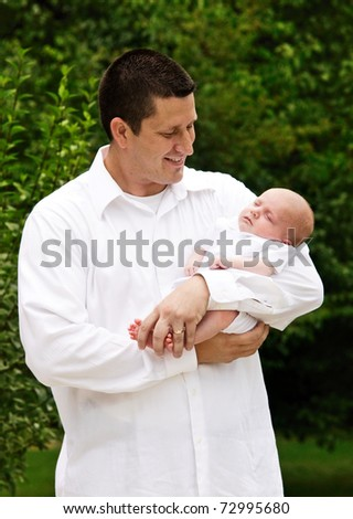 A father holding his newborn baby boy, vertical with shallow depth of field, natural light