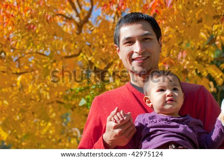 A father is holding his daughter under an autumn tree