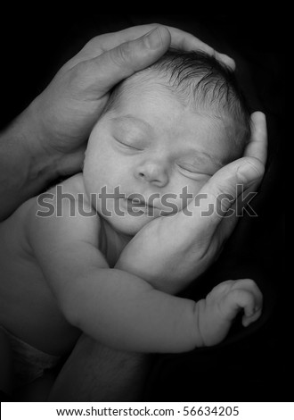 A father is holing a baby newborn in his hands. The infant is sleeping and it is a black and white portrait. The image can represent security, innocence or parenthood.