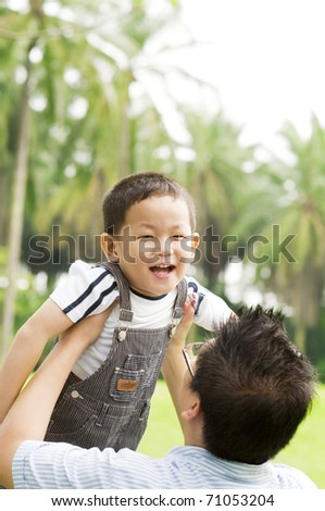A father playing with his child on a nice summer day.