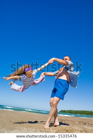 A father playing with his little girl on beach. Vacation, summer time.