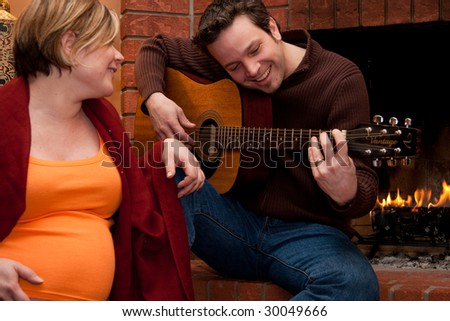 A father plays the guitar for his pregnant wife