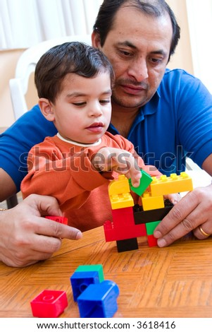A father plays with his son and helps him build with his blocks
