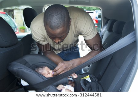 A father putting his newborn daughter into her car seat in the car. He is wearing casual clothing and looking at his daughter.