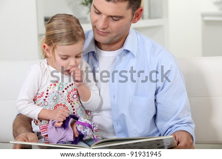 A father reading to her daughter.