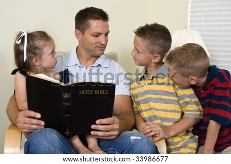 A father reads to his three young children from the Holy Bible.