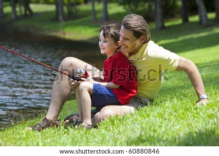 A father teaching his son how to fish on a river outside in summer sunshine