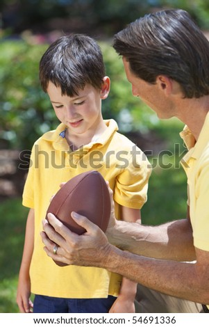 A father teaching his son how to play American football outside in sunshine