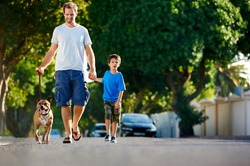 A father walking with his dog and his son in the suburbs