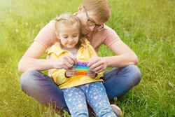 a father with glasses plays with a child in the park on the grass. Silicone toy pop it, neuropsychology and anti-stress, autism, psychological health of children