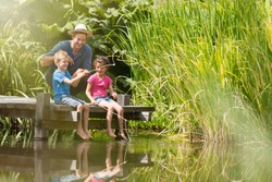 a father with his son and daughter engaged in fishing in a river, they are sitting on a wood pontoon