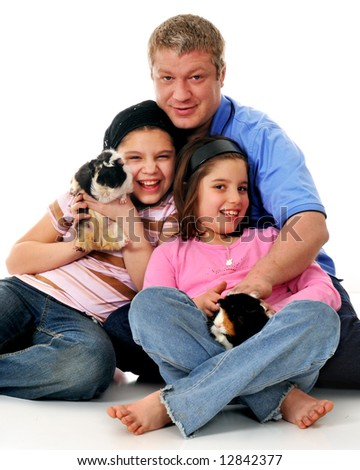 A father with his two daughters having fun with their pet guinea pigs.