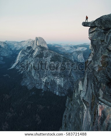 a fearless hiker is standing on ...