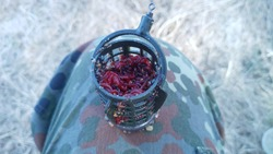 A feeder made of plastic with a lead weight stuffed partly with bait and partly with bloodworm larvae for catching fish with a feeder tackle.