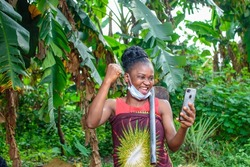 A female african farmer with nose mask and a farming hoe on her shoulder happily looks into a smart phone she's holding in a banana farm or plantation