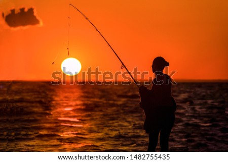 A female angler is fishing on the beach while the Sun is setting on  the ocean.  The sinker is just above the Sun, as if she hooked the Sun on the line.   #1482755435