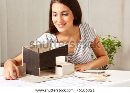 A female architect looking over a model house with blueprints and color swatches on the table