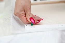 A female artist uses her manicured thumb to push a tack into the back of a blank white canvas. This lifts it off the table once turned, so that it won't stick, after the fluid paint is poured onto it.