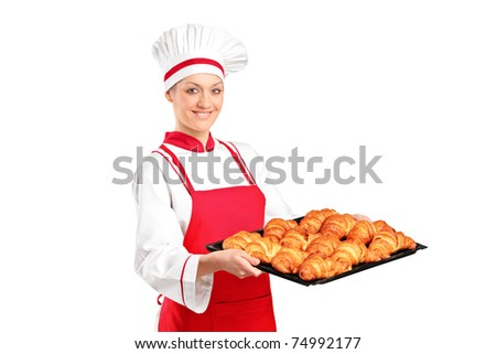 A female baker, wearing red apron, holding freshly baked croissants isolated on white background