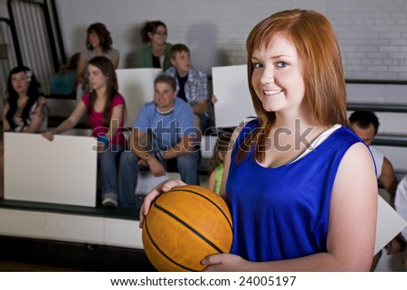 A female basketball player in the school gym, with her home fans in the background.