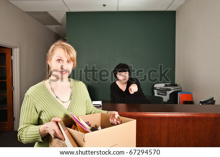 a female boss points angrily to the door as the fired worker looks out in shock while leaving with her belongings