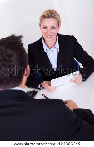 A female business executive smiling at her male colleague.