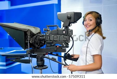 a female cameraman at a studio smiles into camera