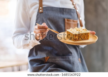 A female chef baking and eating a piece of homemade carrot cake in wooden tray Photo stock ©