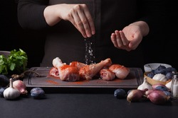A female chef sprinkles fresh raw chicken drumsticks on a dark background with sea salt. Nearby lie the ingredients for cooking: shallots, blue plums, garlic pepper, salt and parsley.