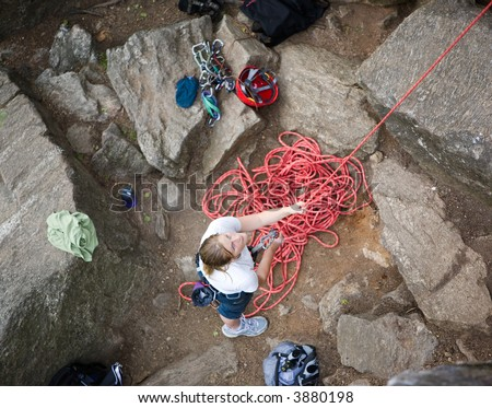A female climber belaying - viewed from above.  A shallow depth of field is used to isolate the climber - with focus on the eyes and head.