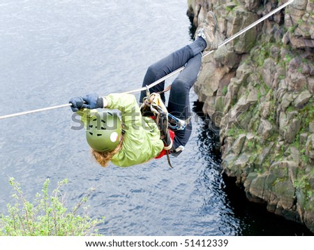 A female climber crosses a gorge along a tyrolean traverse