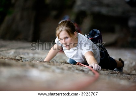 A female climber on a steep rock face looking for the next hold.  Shallow depth of field is used to isolate the climber.