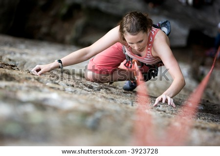 A female climber on a steep rock face viewed from above with the belayer in the background.  Shallow depth of field is used to isolated the climber.
