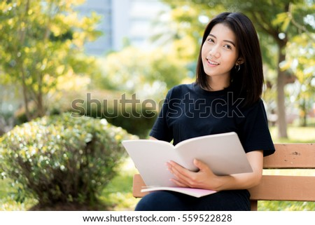 A female college student reading a book while lying on the park #559522828