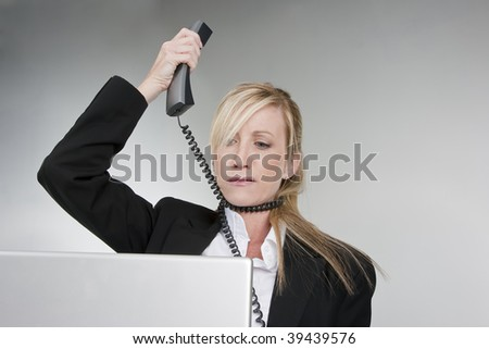 A female customer service agent shows her frustration with the telephone and computer. - stock photo