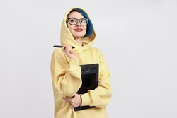 A female designer in yellow hoody holding graphic tablet. The white background